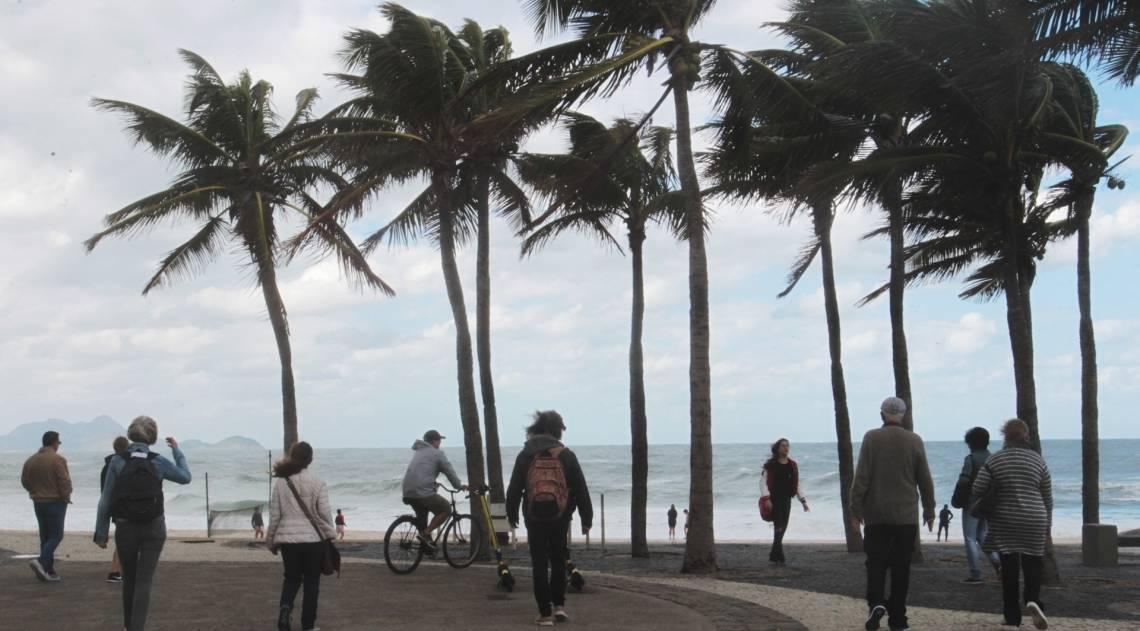 Cariocas e turistas aproveitam o fim de semana na praia mesmo com muito frio e chuva. Na foto turistas no Arpoador.