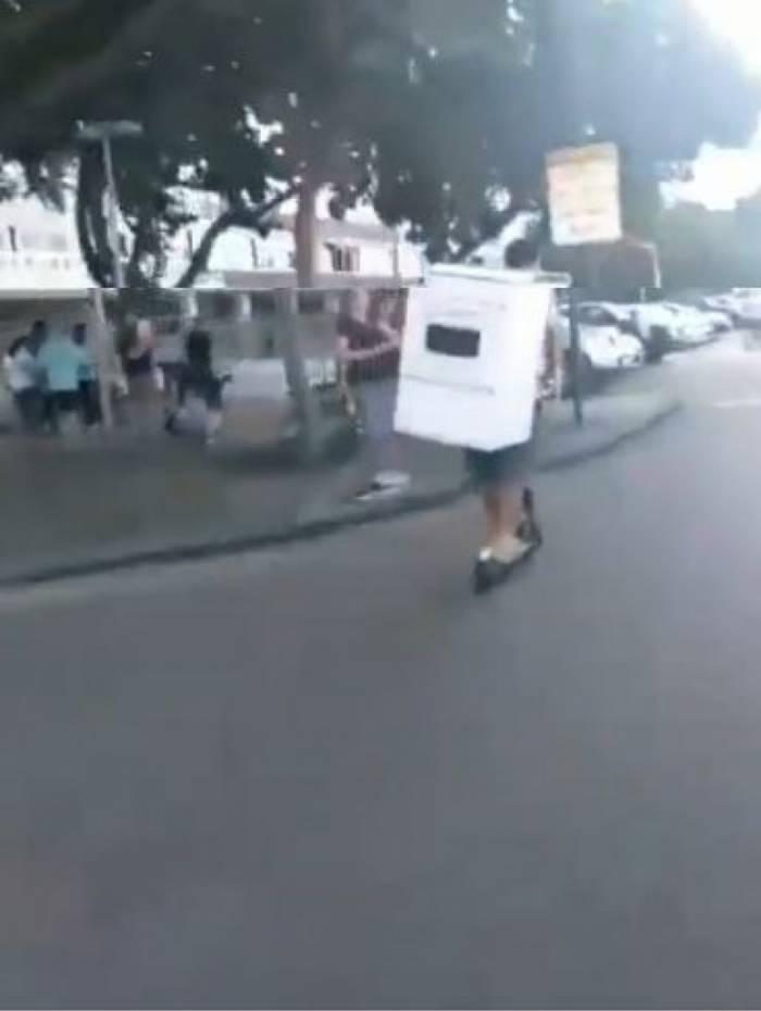 Homem é flagrado levando fogão em um patinete elétrico