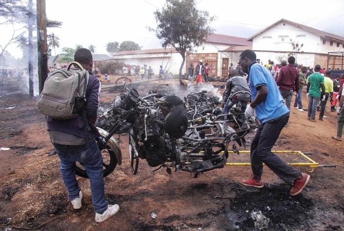 Homens carregam destroços após explosão na Tanzânia