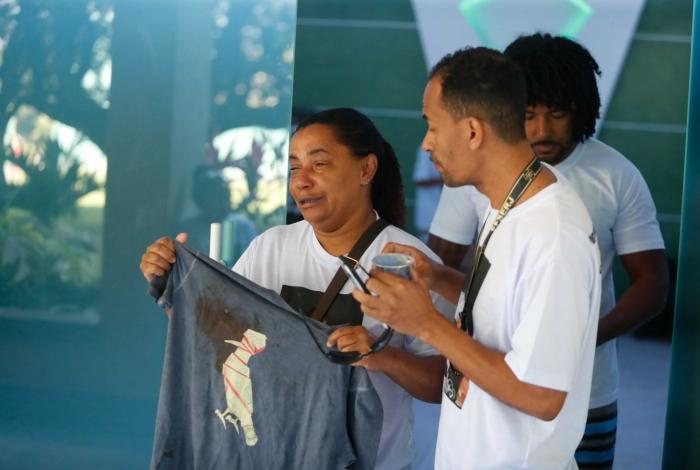 Mãe, pai e irmão mais velho de Gabriel mostram a camiseta que ele vestia quando foi baleado, na Tijuca, na última sexta-feira (9)