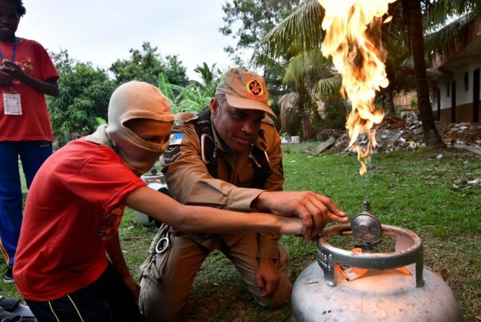 Bombeiro ensina ao estudante como combater o incêndio em botijão de gás