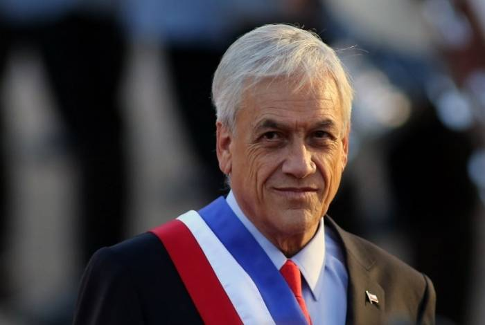 Chilean new President Sebastian Pinera gestures upon arrival at La Moneda presidential palace in Santiago after the inauguration ceremony on March 11, 2018.  / AFP PHOTO / CLAUDIO REYES