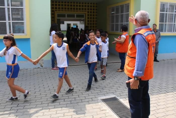 Os alunos repetem o que aprenderam com os agentes da defesa civil e bombeiros na simulação de emergência na escola