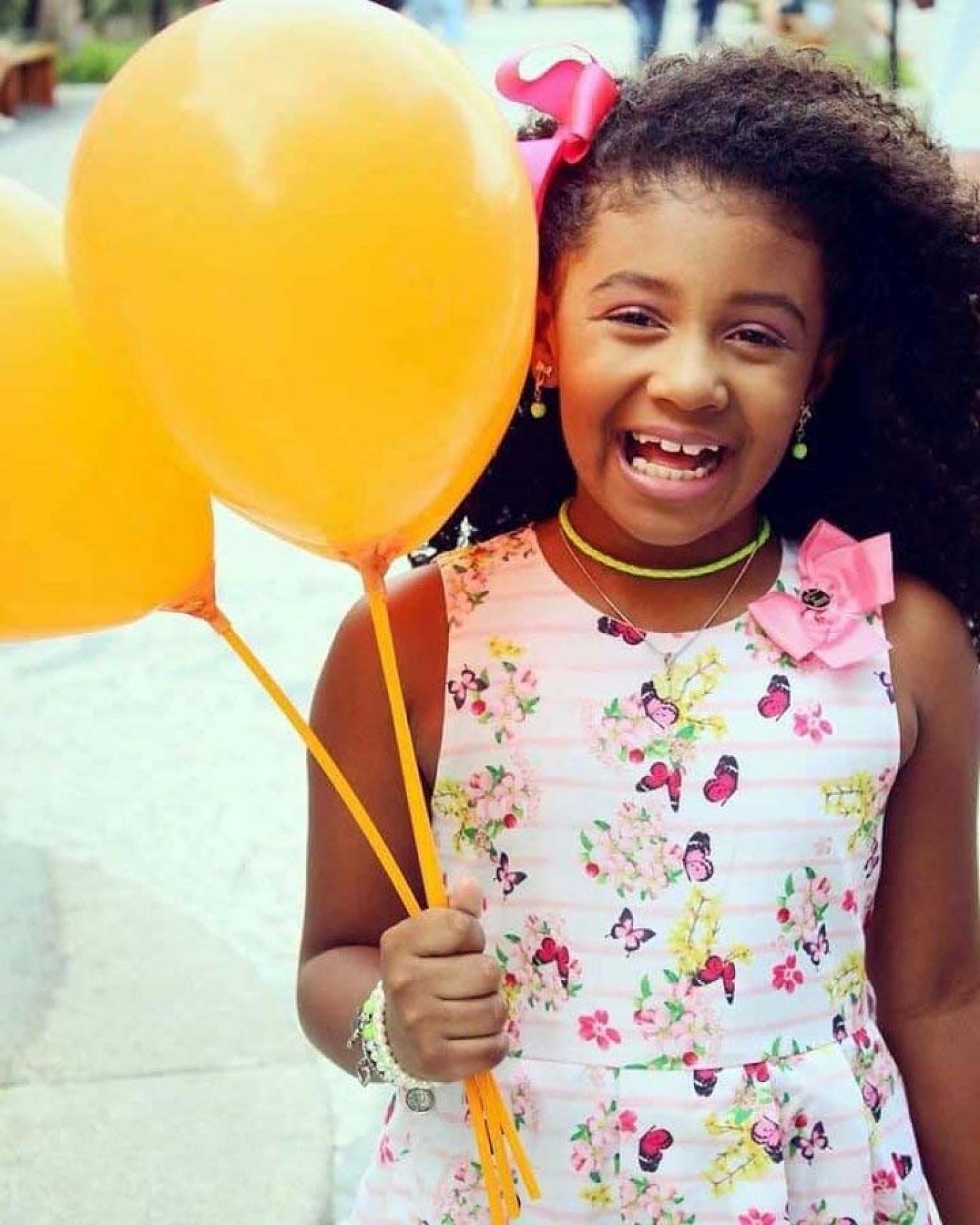 Foto de Agatha Felix, menina negra, sorrindo, segurando balões amarelos.