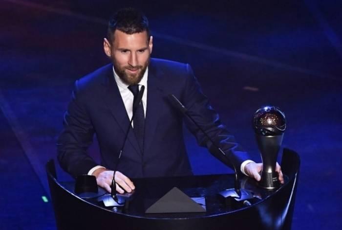 Messi ao lado do prêmio de melhor do mundo