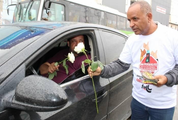 Funcionário entrega rosa branca ao motorista na Via Light