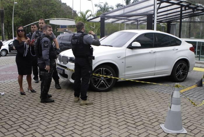 A delegada Adriana Belém e agentes da 16ª DP (Barra da Tijuca) fazem perícia no carro da vítima, atingido por pelo menos três disparos