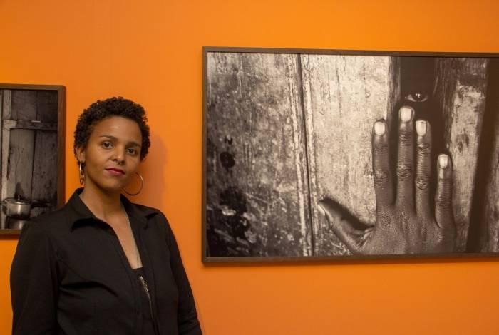 Valda Nogueira ao lado de foto da exposição 'Através do Olhar', no Sesc de Madureira. Artista desenvolvia trabalhos documentais