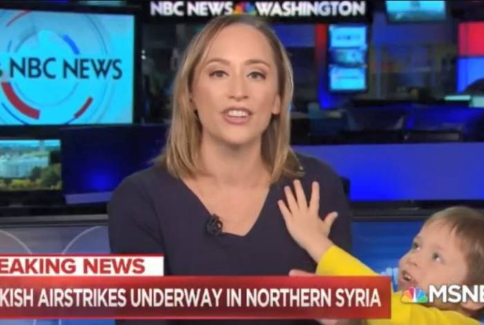 Menino estica os braços para a mãe durante jornal ao vivo