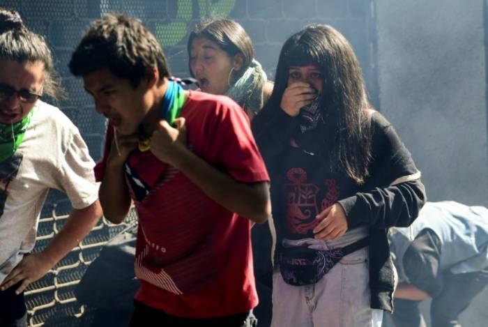 Manifestantes se afastam do gás lacrimogêneo durante confronto com a polícia em Santiago