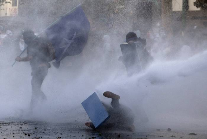 Demonstrators clash with security forces during the so-called 'Mourning March' in Santiago on November 01, 2019, to protest against the death of 23 people after more than ten days of civil unrest. - Chile's government met with opposition leaders Thursday in a fresh bid to end deadly protests that forced the country to abandon hosting two major economic and climate summits, but leftist parties poured scorn on the efforts. The unrest started with protests against a rise in transport tickets and other austerity measures and descended into vandalism, looting, and clashes between demonstrators and police. (Photo by CLAUDIO REYES / AFP)