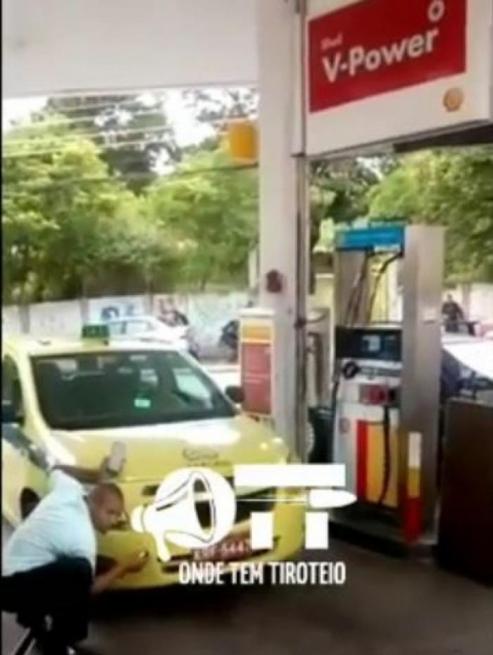 Taxista se protege dos tiros em um posto de gasolina no Jacaré