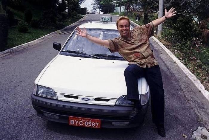 Gugu posa com um dos carros usados no famoso quadro