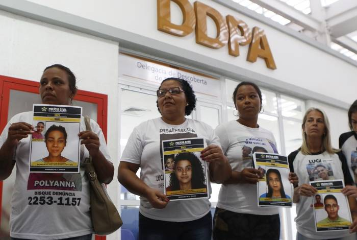 Mães seguram cartazes que mostram fotos do antes e da simulação atual dos rostos de seus filhos