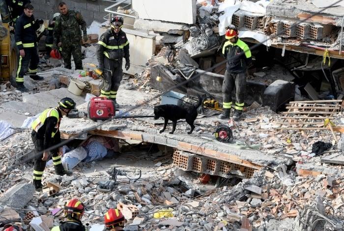 Equipes de resgate italianas buscam sobreviventes através dos escombros de um prédio desabado em Thumane, noroeste da capital Tirana, depois que um terremoto atingiu a Albânia
