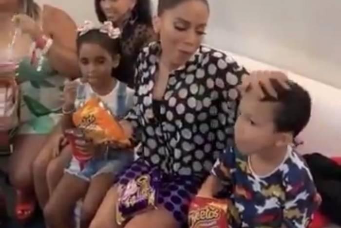 Anitta com a mão suja de salgadinho no cabelo do sobrinho