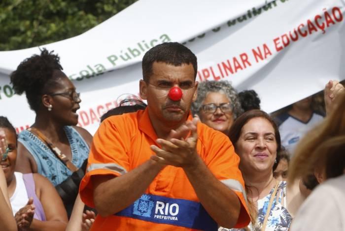 Manifestante com roupa de gari e nariz de palhaço protesta em frente à sede da Prefeitura do Rio