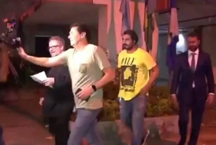 Thiago Lacerda (de amarelo) deixa a delegacia após ser liberado