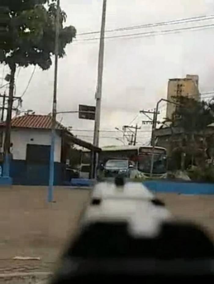 Homem aponta pistola na direção de uma viatura da Polícia Militar