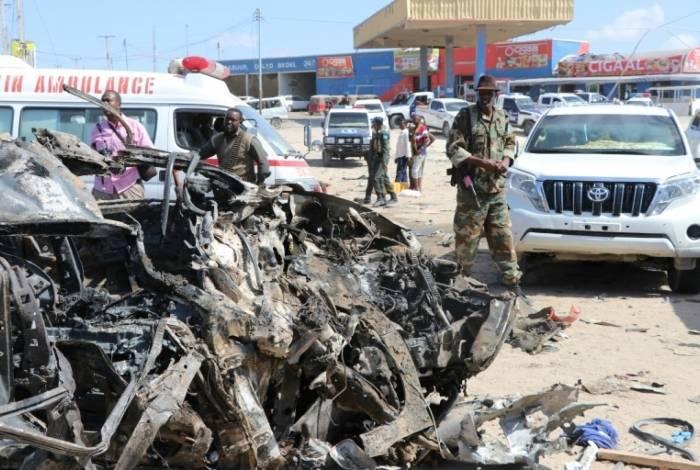 Soldado passa perto de carro destruído em ataque na Somália