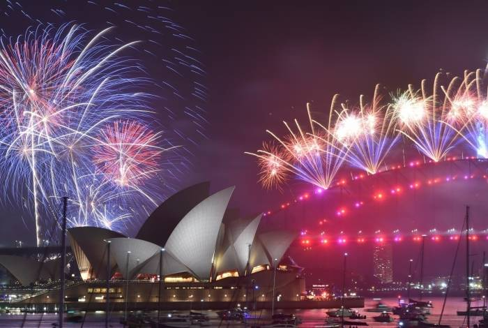 New Year's Eve fireworks erupt over Sydney's iconic Harbour Bridge and Opera House (L) during the fireworks show on January 1, 2020. (Photo by PETER PARKS / AFP)       Caption