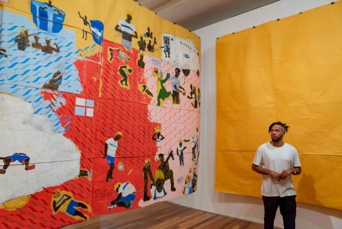 Maxwell Alexandre posa com obra da exposição