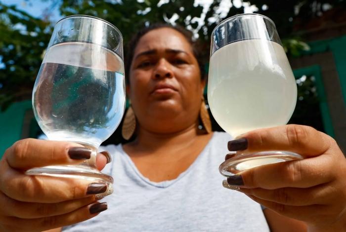 Jaqueline Leocadio, moradora do bairro de Paciência, mostra a diferença entre a água mineral e a que está saindo das torneiras