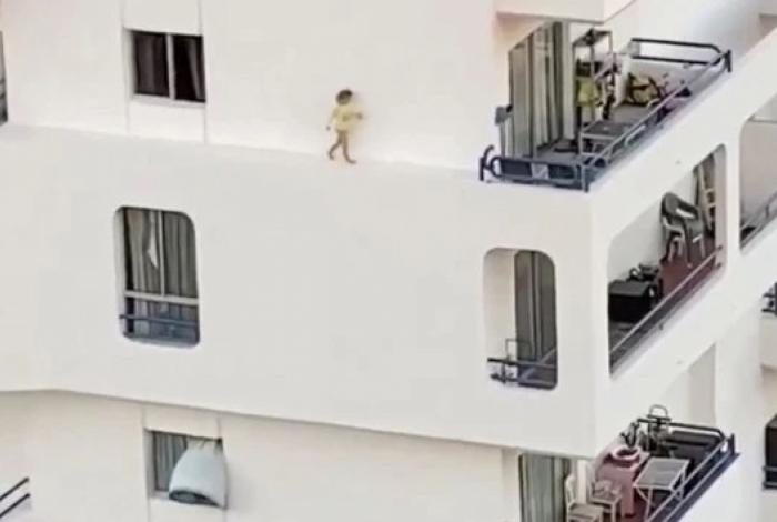Criança cruza parapeito externo de prédio