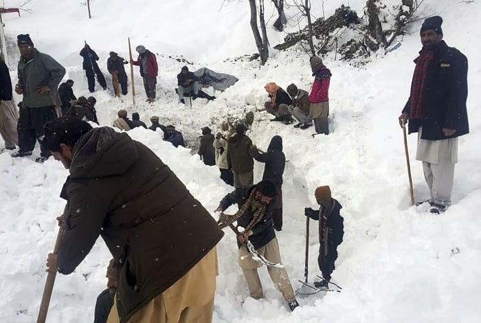 Residentes locais procuram as vítimas de avalanches na neve no Vale Neelum, na Caxemira administrada pelo Paquistão em 15 de janeiro de 2020.