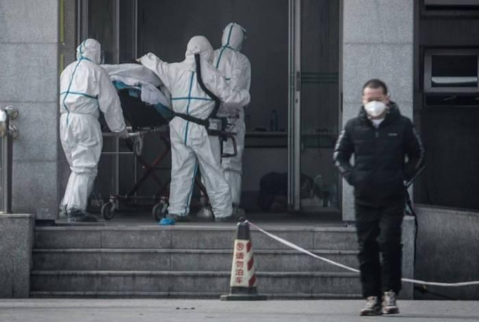 Funcionários de um hospital carregam paciente na cidade de Wuhan, no centro da China