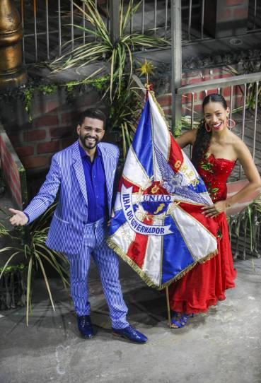 Phelipe Lemos e Dandara Ventapane posam no barracão da União da Ilha. Uma das esculturas do desfile, sobre a favela, é um casal de sambistas