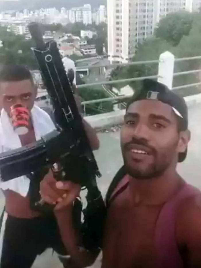 Criminosos aparecem nas imagens com um fuzil e uma pistola