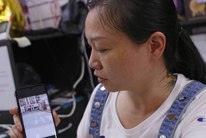 A comerciante Zhang mostra imagens da sua cidade natal na China: as ruas lá estão vazias