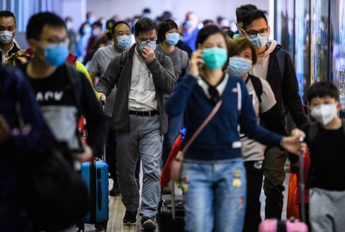 Passageiros usam máscaras ao chegar de Shenzhen a Hong Kong na estação MTR Lo Wu, horas antes do fechamento da fronteira com Lo Wu em Hong Kong