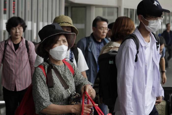 Passageiros desembarcam no Aeroporto do Galeão com máscaras