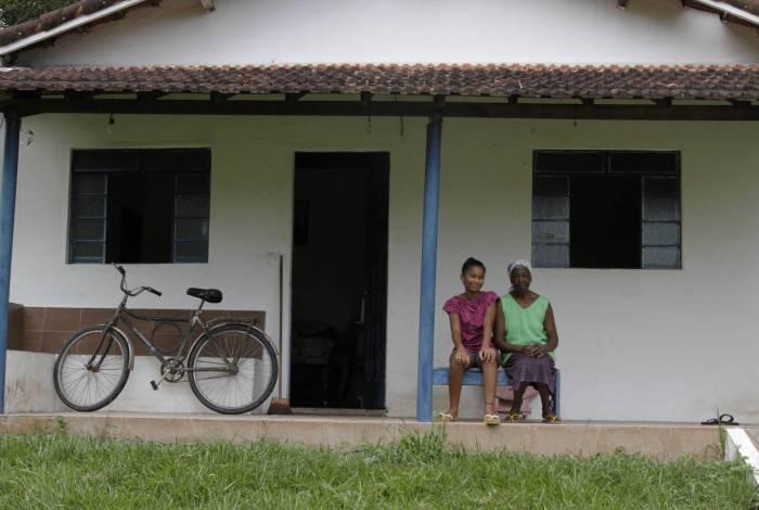 Ligação de água e esgoto da casa de Maria de Lourdes (na foto, com a neta) vão juntas para a fossa no quintal