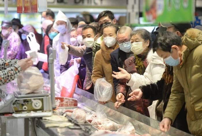 Pessoas que usam máscaras protetoras compram em um supermercado em Wuhan, o epicentro do surto de um novo coronavírus, na província central de Hubei, na China