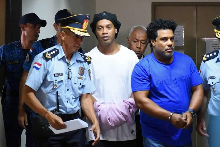 Ronaldinho e o irmão, Assis, chegam algemados para audiência