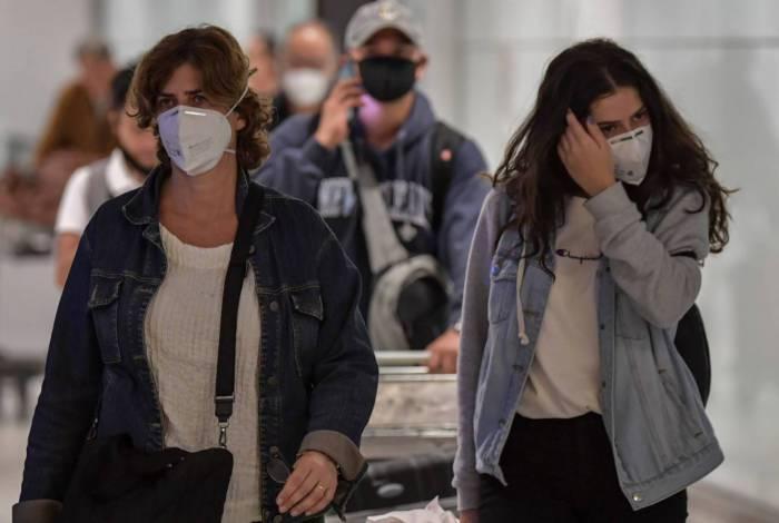 Passageiros desembarcam com máscaras no aeroporto de Guarulhos, em São Paulo