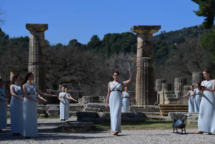 Women dressed as a priestesses take part in the Olympic flame lighting ceremony in ancient Olympia, ahead of Tokyo 2020 Olympic Games on March 12, 2020. (Photo by ARIS MESSINIS / AFP)