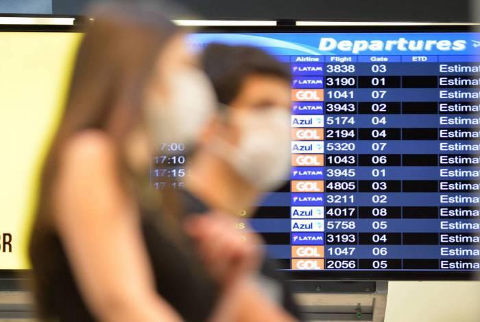 Passageiros usando mascaras no aeroporto