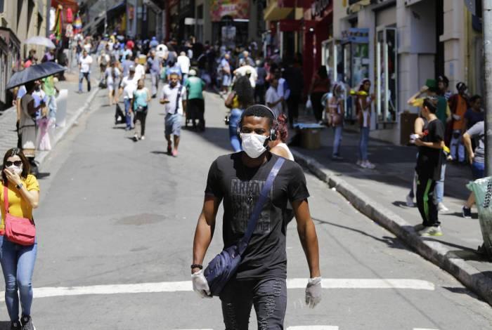 Na região central da cidade de São Paulo, pessoas circulam com máscaras e luvas