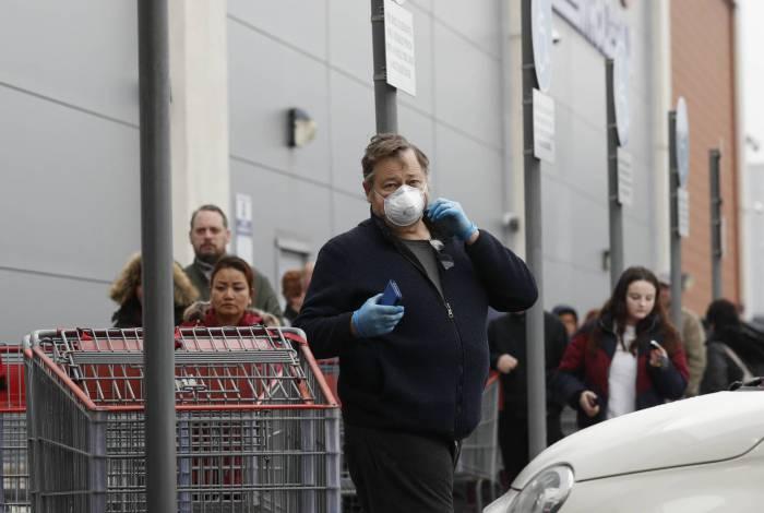 Clientes esperam em uma longa fila para entrar em uma loja atacadista da Costco em Farnborough, oeste de Londres, em 19 de março de 2020