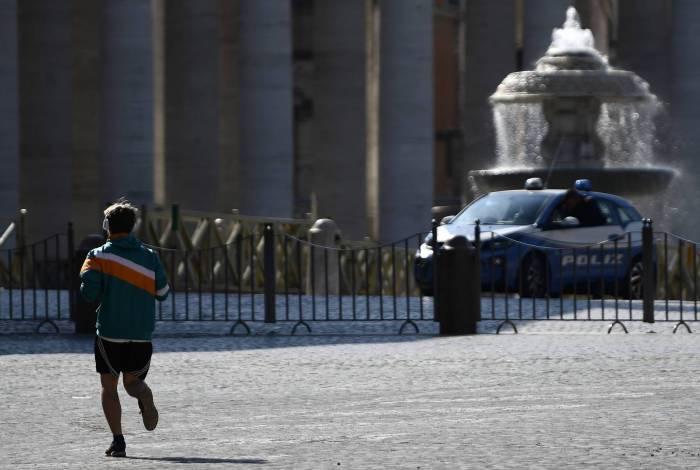 Homem corre enquanto um carro da polícia nacional italiana patrulha a Praça de São Pedro no Vaticano