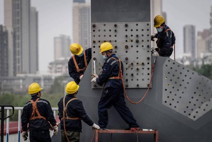 Funcionários usando máscaras trabalham no canteiro de obras de uma ponte em Wuhan, na província central de Hubei, na China, em 24 de março de 2020