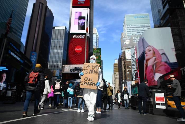 Um homem com roupa de proteção e uma máscara segura uma placa dizendo 'o fim está próximo, ligue para a vovó' na Times Square em 14 de março de 2020 em Nova York