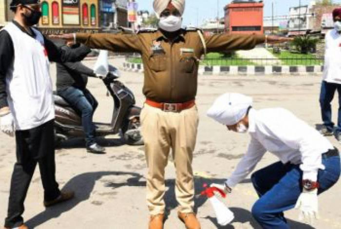 Voluntário espirra desinfetante em policial em uma rua em Amritsar, na Índia