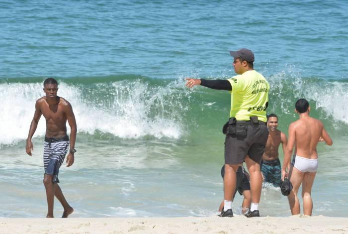 No Arpoador, PM manda grupo de jovens sair da água e deixar a praia. Em outras praias da orla também teve gente desobedecendo às medidas