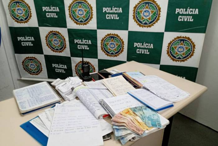 Na casa da mulher presa em flagrante foi encontrado cadernos de anotações de cobrança e material de contabilidade do grupo, além de dinheiro
