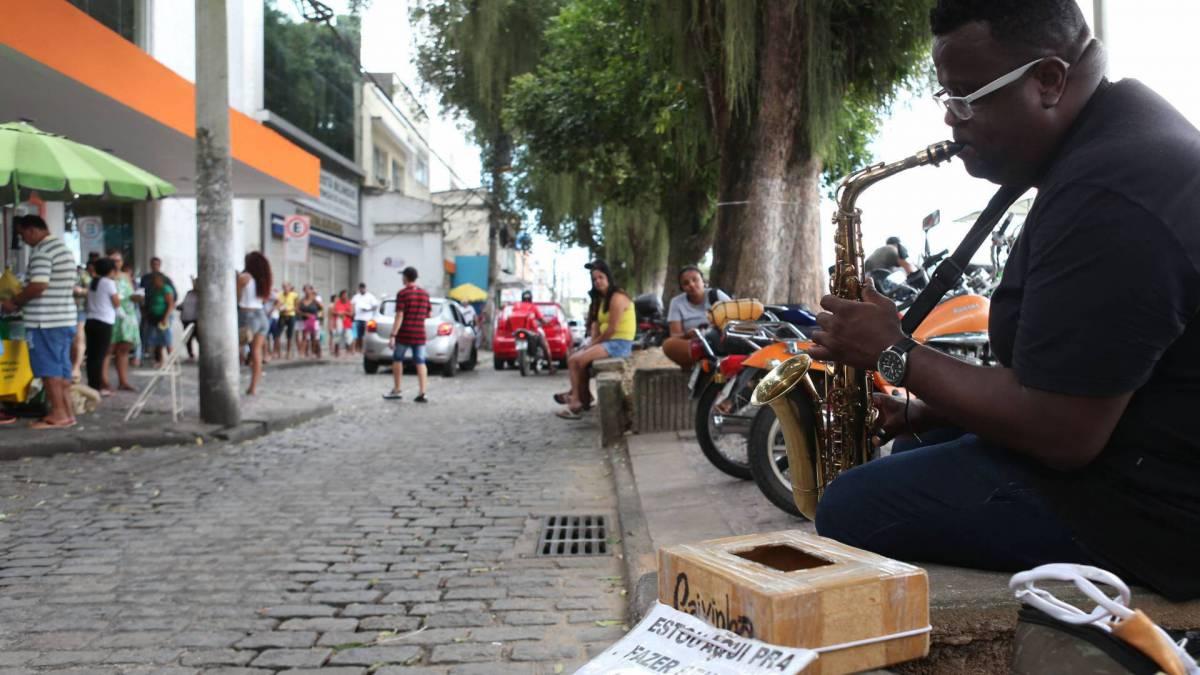 Rio,03/04/2020-COVID-19-CORONA VIRUS, SANTA CRUZ,Av: Felipe Cardoso, Rapaz toca sax em uma praca em Santa Cruz, por um dia mais feliz. Na foto, Ronaldo Martins tocando sax, com fila de banco ao fundo.Foto: Cleber Mendes/Agência O Dia